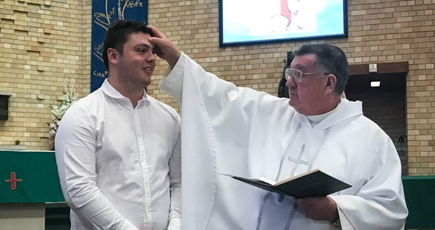 om Squire is confirmed with chrism by Mons Brian Rayner, parish priest of St Catherine Labouré parish, Gymea, where Tom volunteered to pack shipping containers for impoverished communities in Fiji. PHOTO: Moira Loader