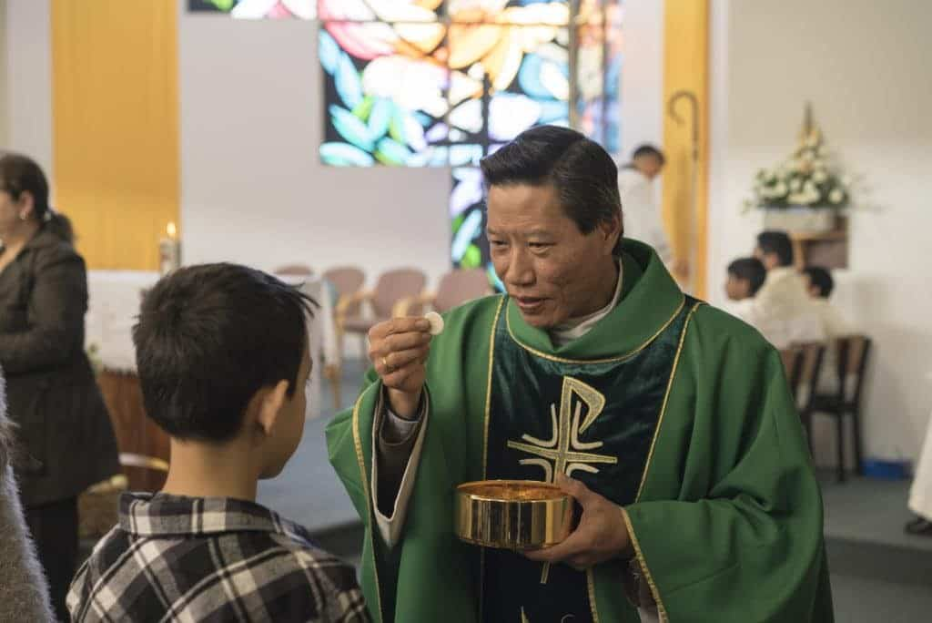 Fr Remy Lam Son Bui, parish priest of the nearby parish of All Saints, Liverpool, holds up the host as he gives Communion during Mass at St Francis Xavier, Lurnea. Photo: Patrick J Lee